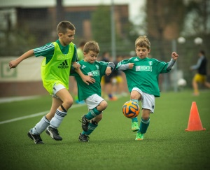 Three boys playing soccer.