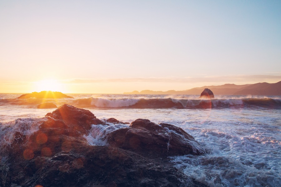 Waves breaking over rocks at sunset